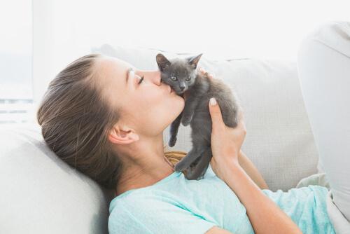 Mulher beijando filhote de gato