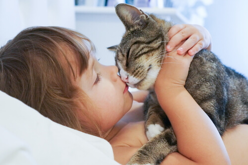 Menina beijando gato