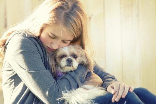 mulher abraçando seu cão