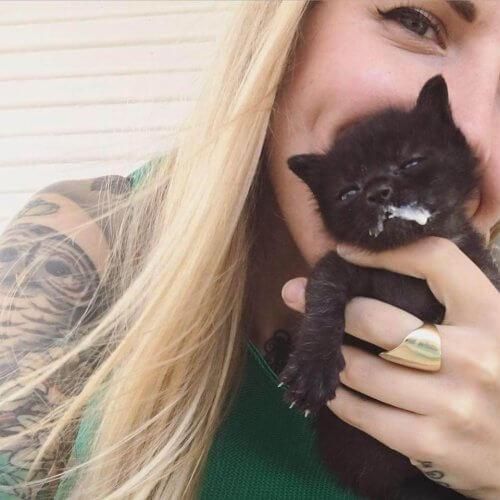 Kitten Lady com um filhote de gato preto