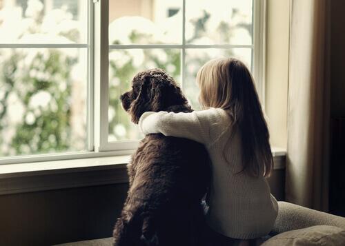 Menina abraçada a um cachorro