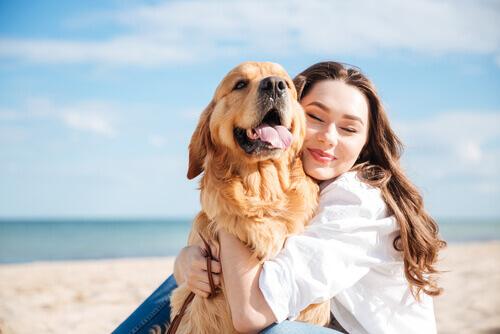 Dona abraçando cachorro na praia