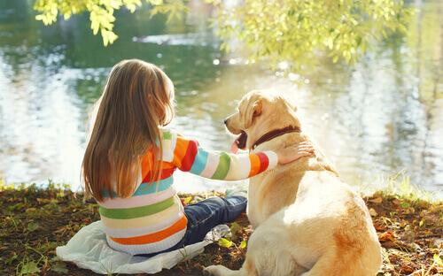 Menina com cachorro na frente de lago