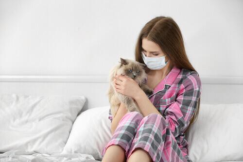 Mulher com máscara e alergia a gatos, com gato no colo
