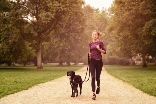 mulher correndo com cachorro: um dos benefícios de ter um animal de estimação