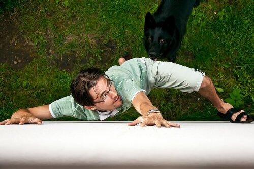 Homem assustado fugindo de um cachorro