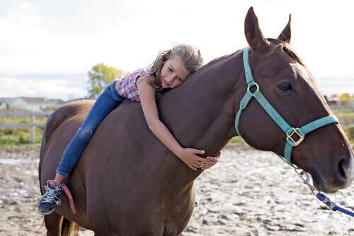 Equoterapia: menina abraçando cavalo