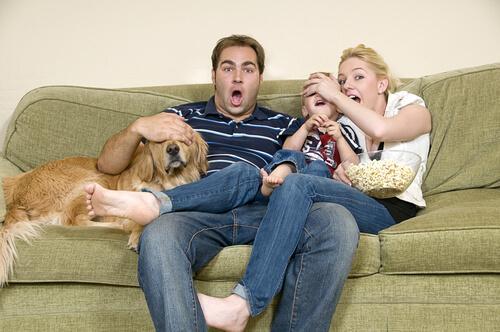 Família assistindo a um filme com cachorro