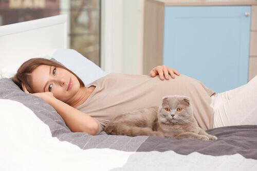 Mulher grávida com gatinho na cama