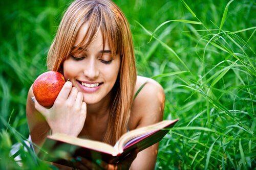 Mulher lendo com maçã