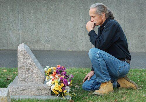 Homem diante de túmulo