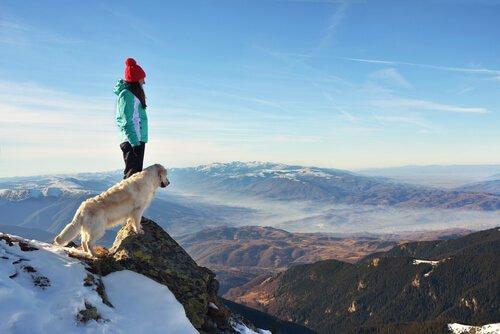 Mulher com cachorro no pico de uma montanha