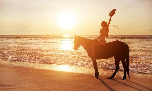 Mulher andando de cavalo na praia