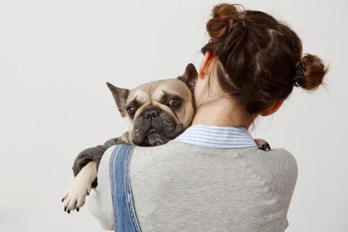 Dona abraçando cachorro