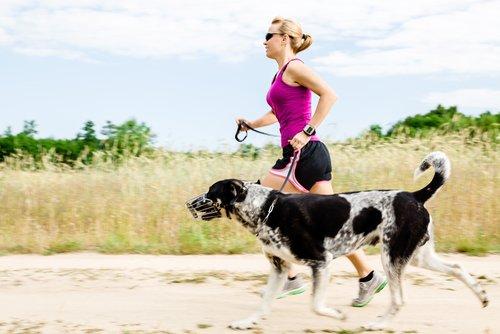 Mulher correndo com seu cão na areia