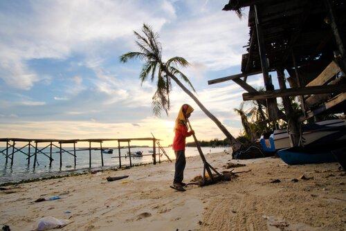 Mulher varrendo praia