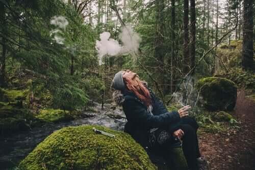 Mulher fumando em floresta
