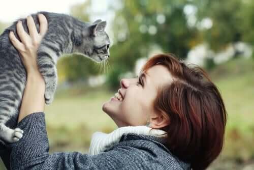 Mulher sorrindo para o seu gato