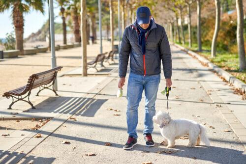 Homem levando animal de estimação para passear durante a quarentena.